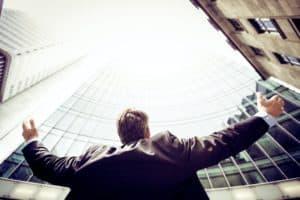 איש עסקים מביט אל השמיים ומרים ידיים